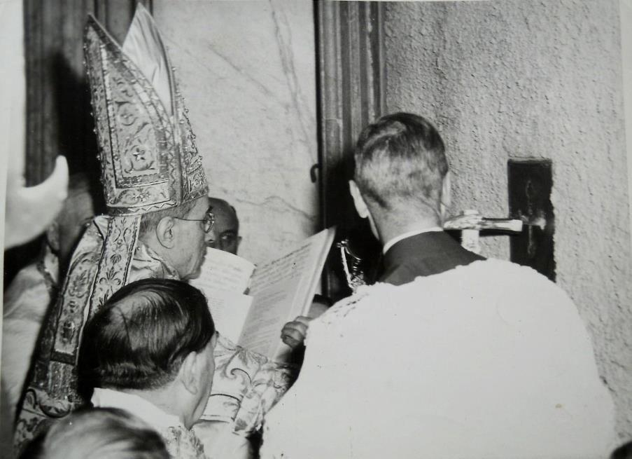 Die heilige Pforte wird vom Papst zu Beginn des heiligen Jahres mit drei symbolischen Hammerschlägen geöffnet. Papst Pius XII und die Porta Santa.